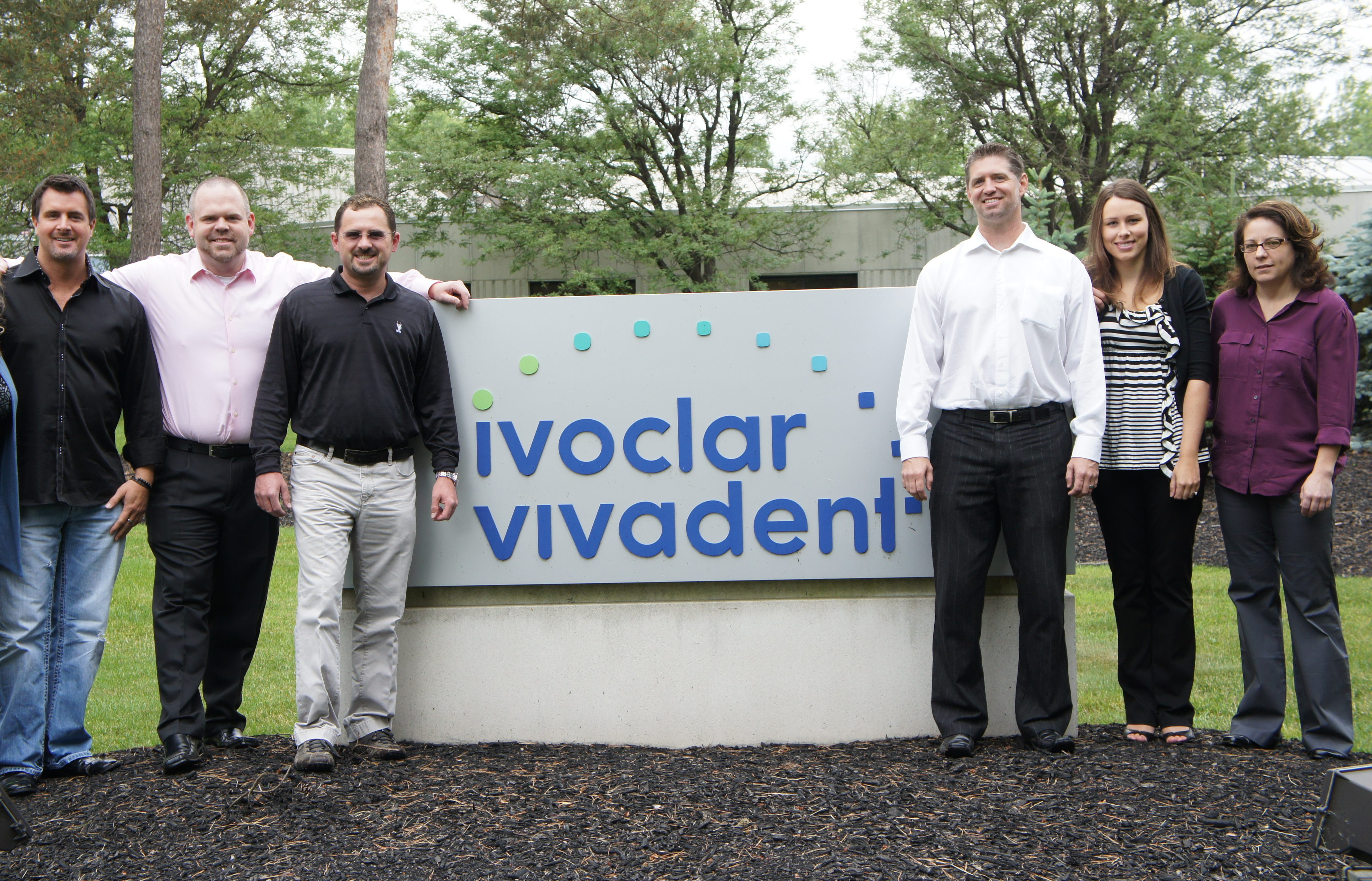 team in front of ivoclar vivadent sign