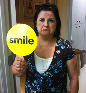 Woman frowning while holding up yellow smile sign